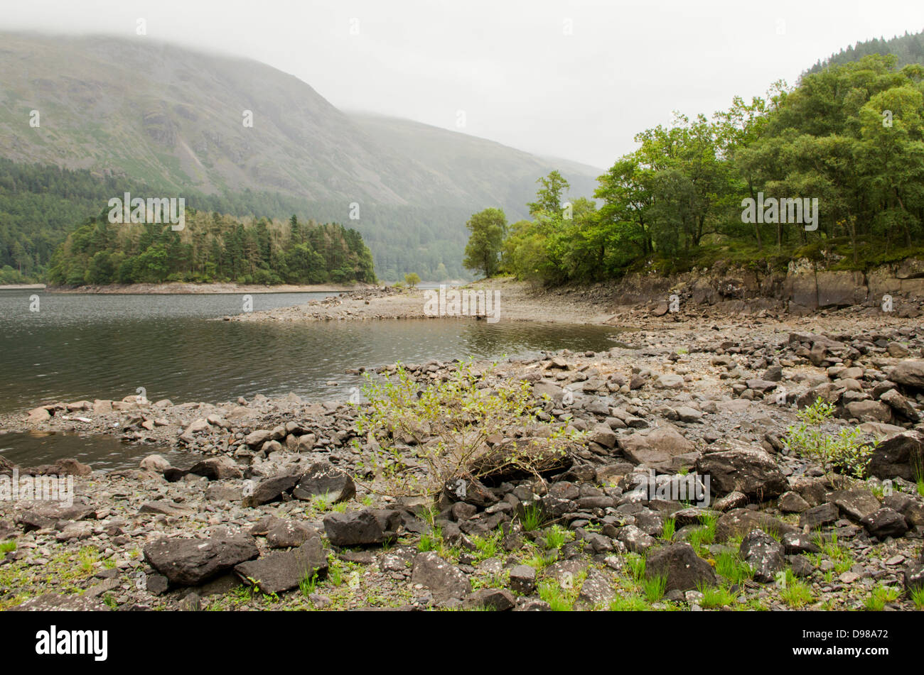 Low water level in Thirlmere reservoir after a dry winter and spring. Bare rocks and island. - Stock Image