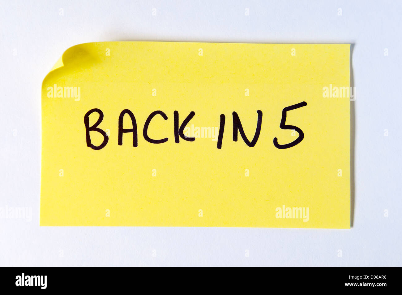 Back in 5 written on a yellow post it note - Stock Image