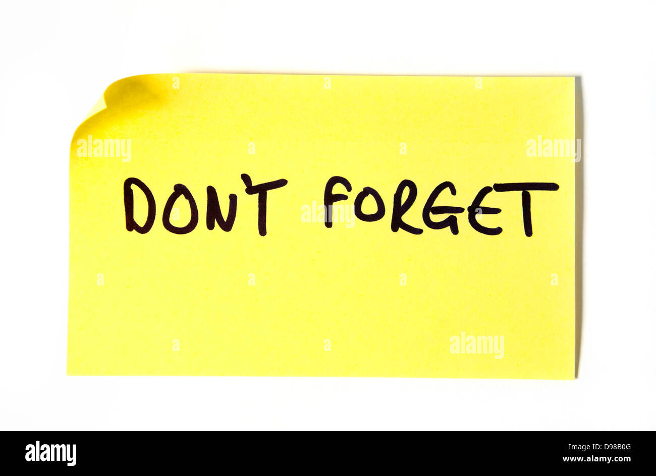 Don't Forget written in capital letters on a yellow post it note. Stock Photo