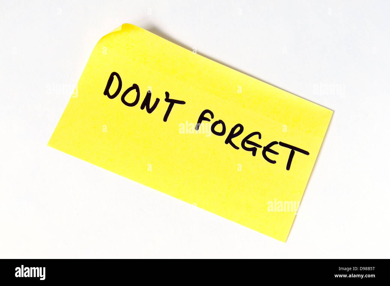 Don't Forget written in capital letters on a yellow post it note. - Stock Image