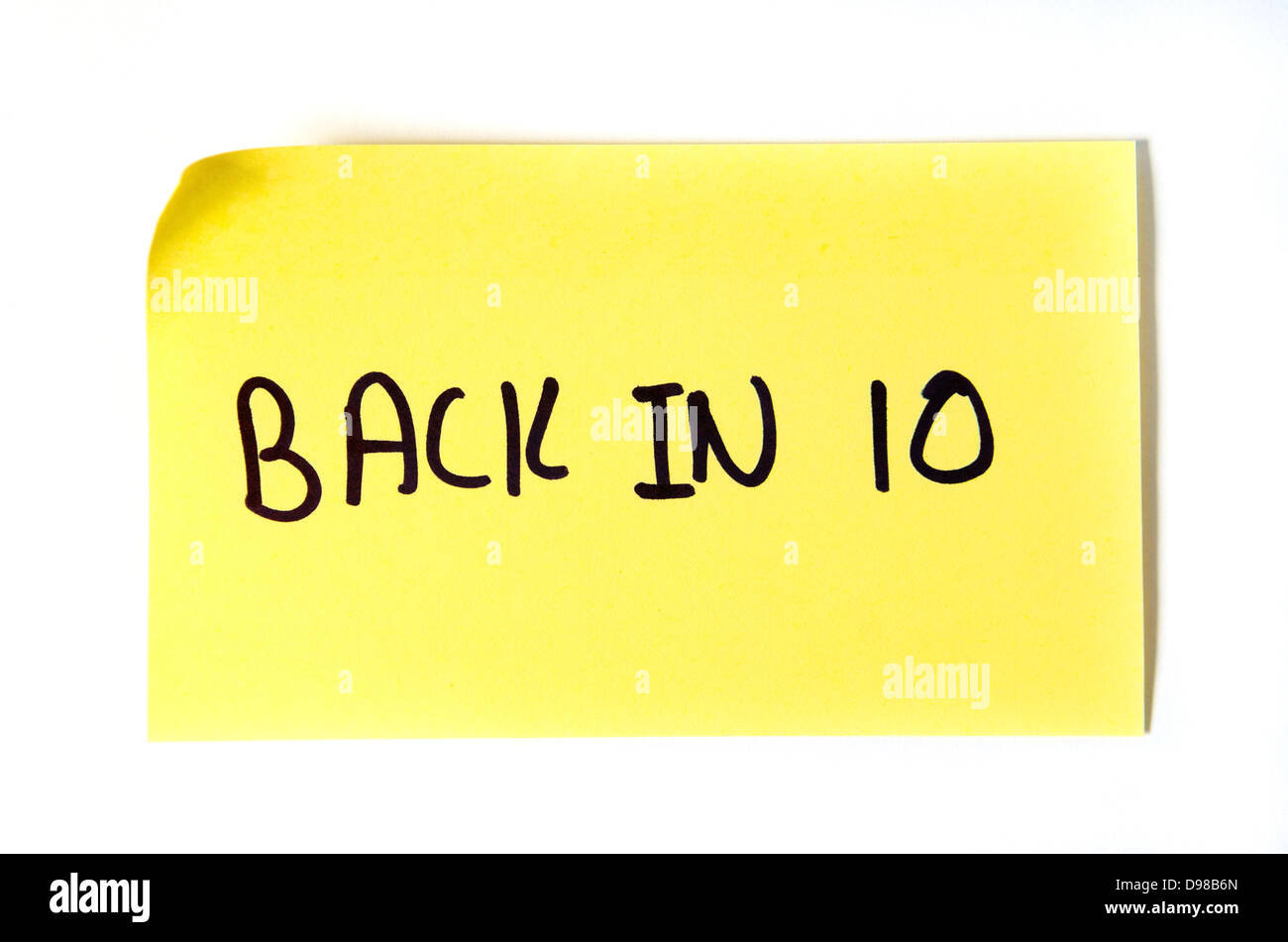Back in 10 written on a yellow post-it note - Stock Image