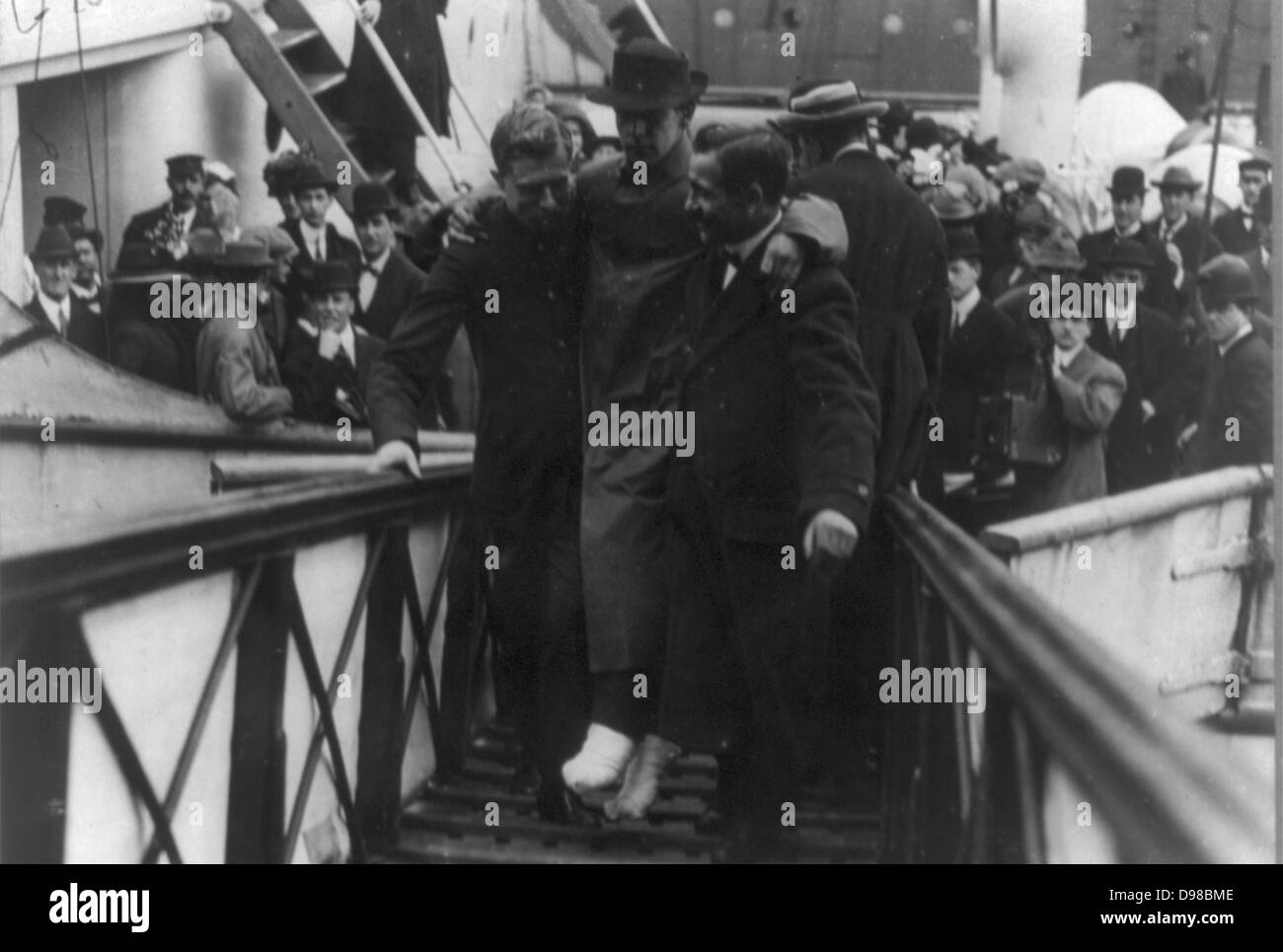 Harold Bride, surviving wireless operator of the TITANIC, with feet bandaged, being carried up ramp of ship]. Date - Stock Image