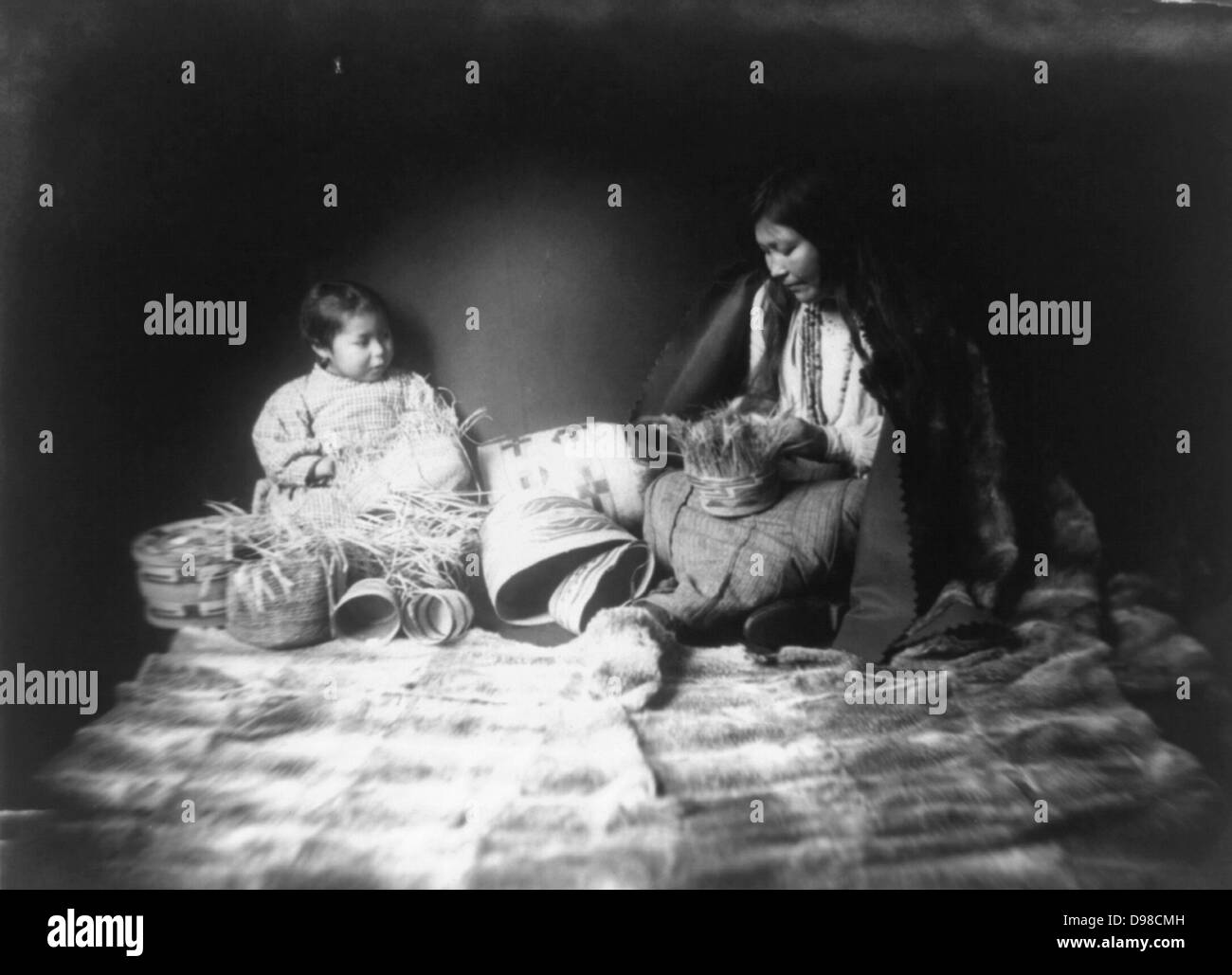 Indian woman and child weaving baskets. - Stock Image