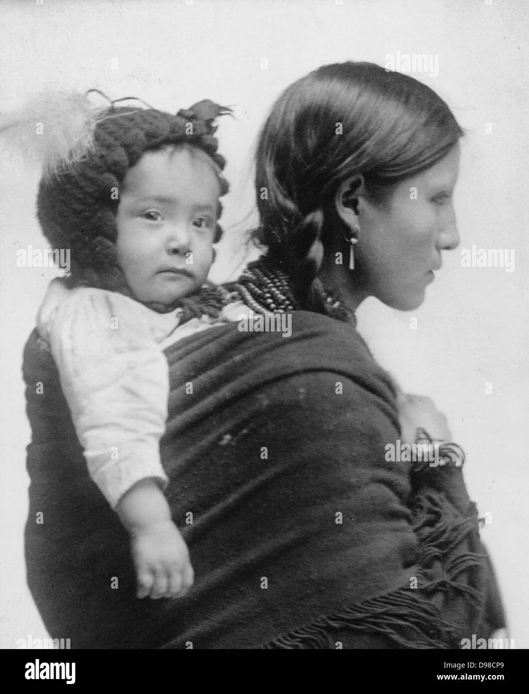 Native American woman from the Plains region, half-length portrait, facing right, with baby on her back. 20th century - Stock Image