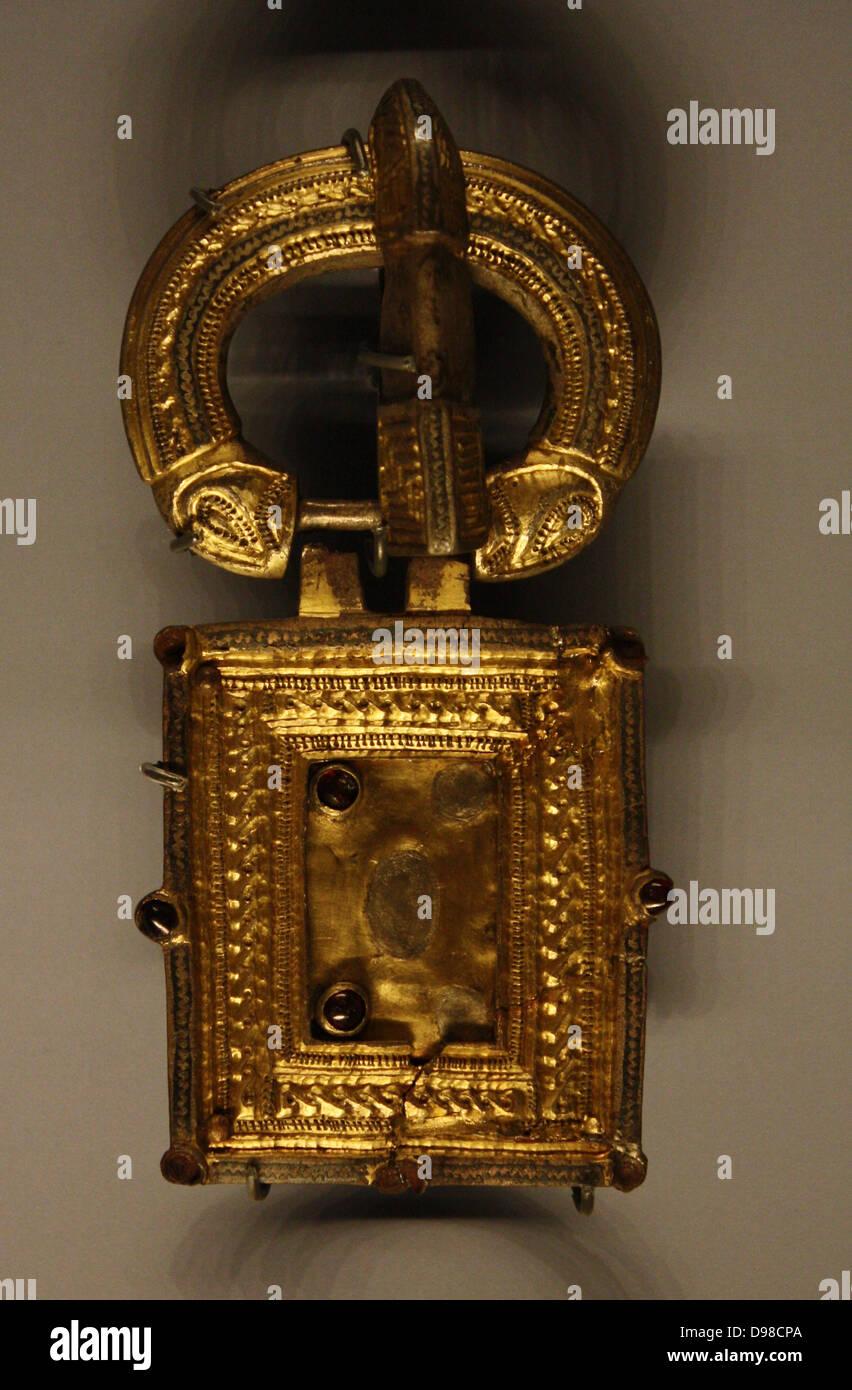 Buckle, silver gilt and garnet.  500-600, Belluno, Italy. - Stock Image