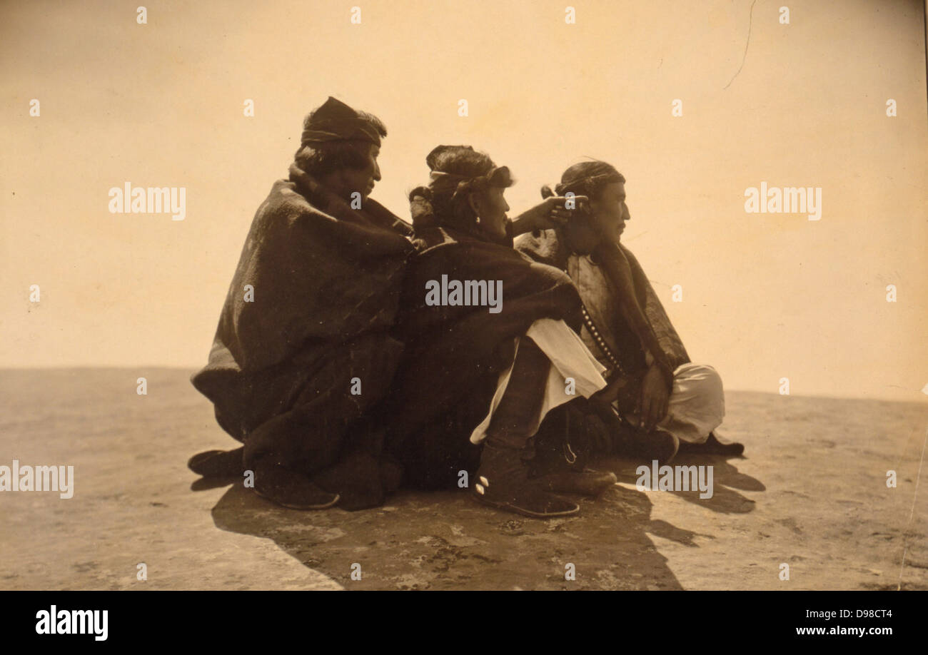 Three Navajo men, seated on ground, turned right, c1904. Photograph by Edward Curtis (1868-1952). - Stock Image