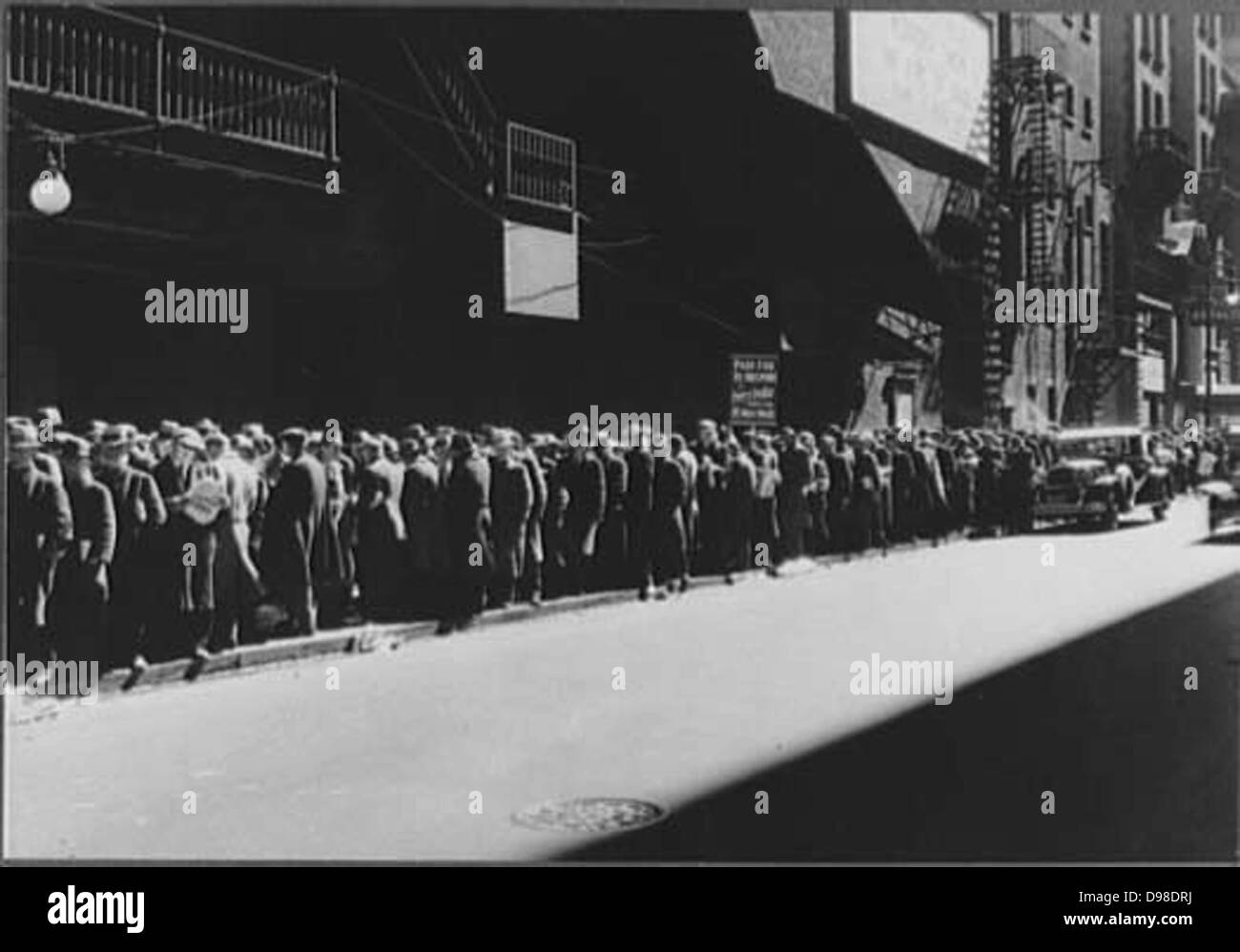 America in the Great Depression, 1930s. Men queue for a five-cent meal. Those on left of sign will get their meal, - Stock Image