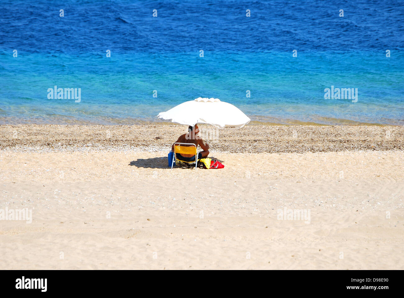 Deserted sandy beach with one solitary male sunbather sheltering under a parasol with turquoise blue sea in the - Stock Image