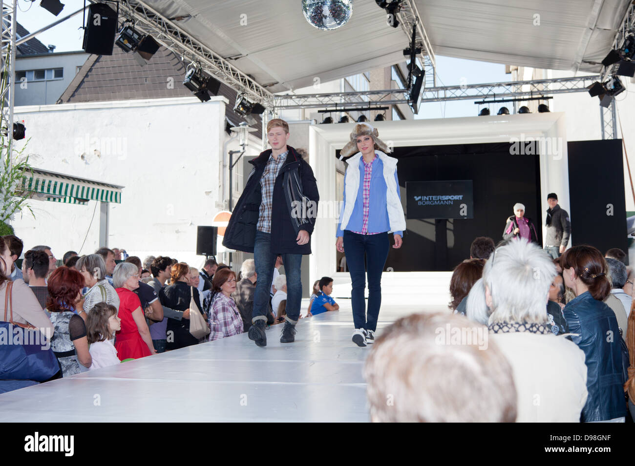 Male and female fashion models being watched by the public on an outdoor catwalk at the open-air event of Krefeld - Stock Image