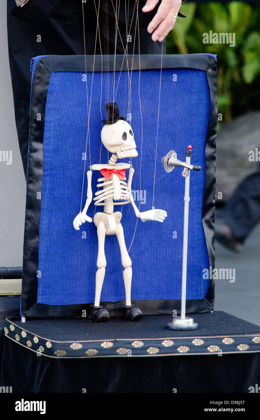 Skeleton puppeteer singing in the street. - Stock Image