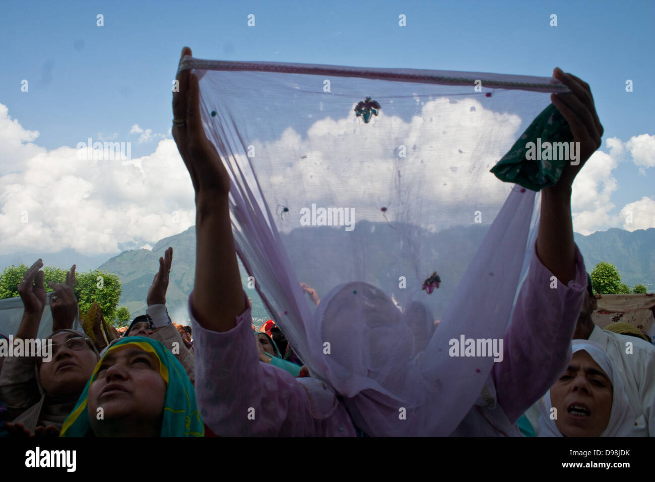 Srinagar, Indian Administered Kashmir 14th june  2013. A woman raises her hands in prayers as a holy relic(unseen) Stock Photo