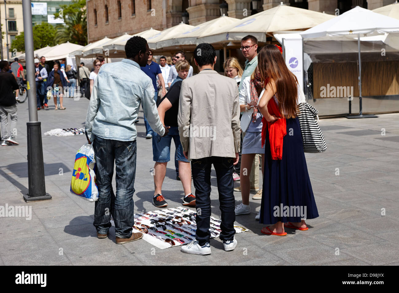 african immigrant street seller selling sunglasses to tourists barcelona catalonia spain - Stock Photo