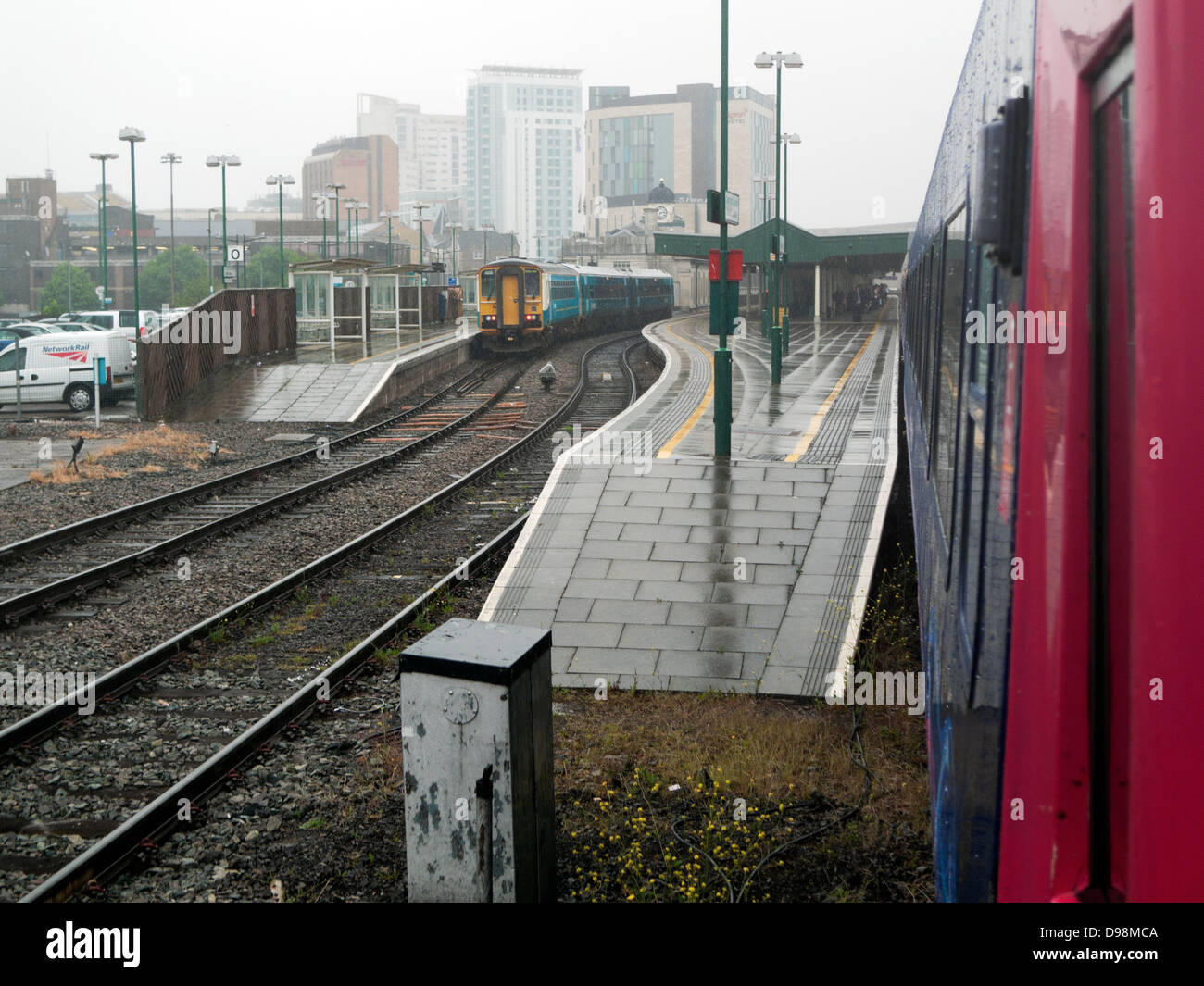 View of the rail tracks train track and side of a Great Western train approaching railway station and city buildings - Stock Image