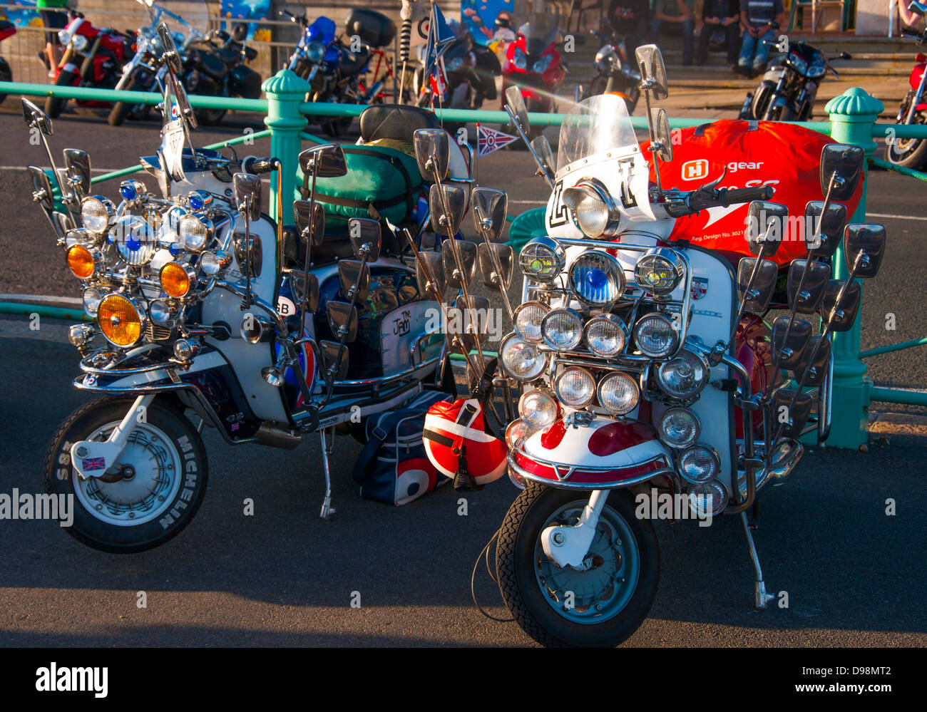A pair of mod scooters, adorned with multiple lights and mirrors, parked near Brighton promenade, England, UK. - Stock Image