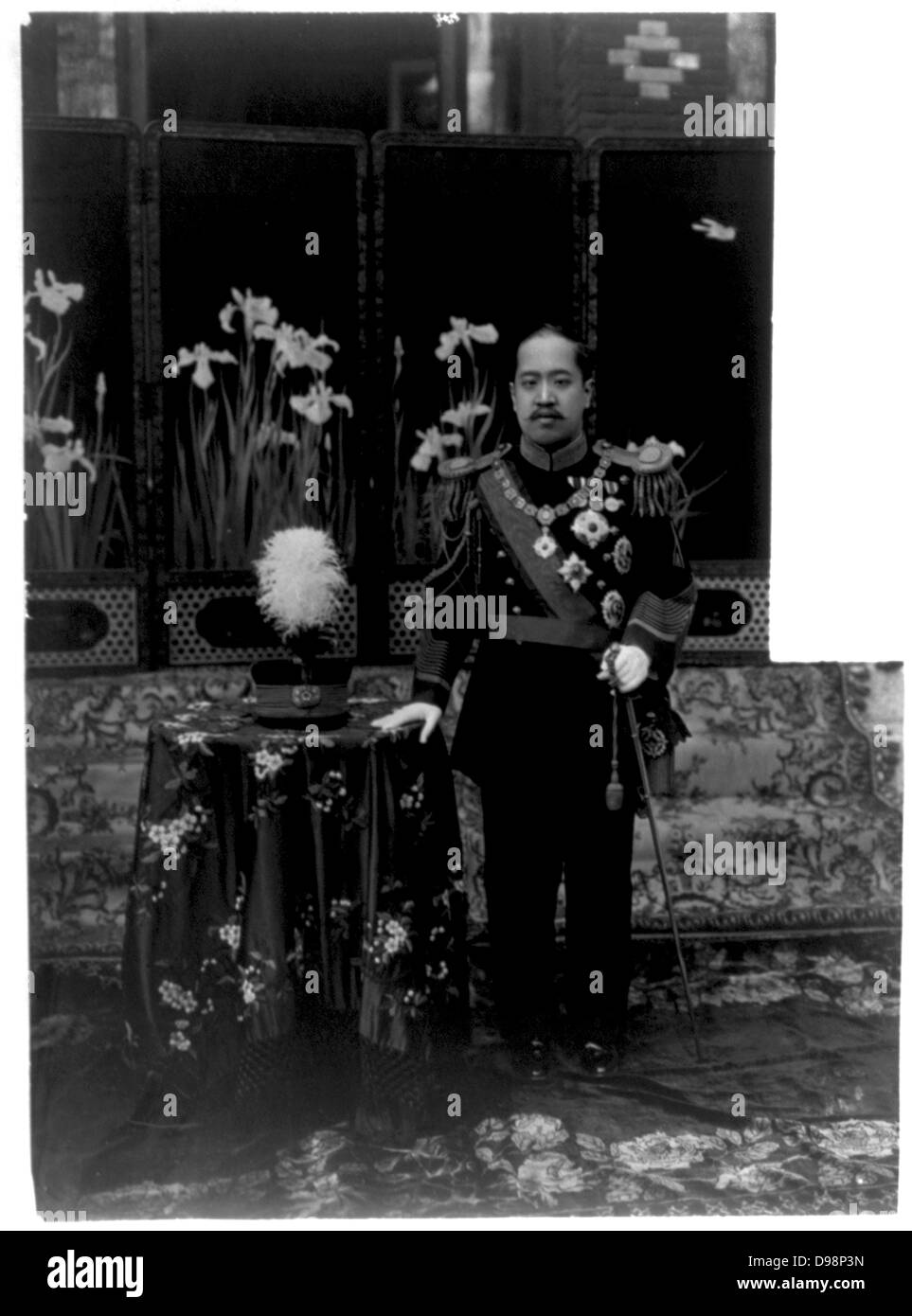 Kojong, Emperor of Korea (1852-1919) in uniform of a Korean general. Full length of Emperor standing beside table. - Stock Image
