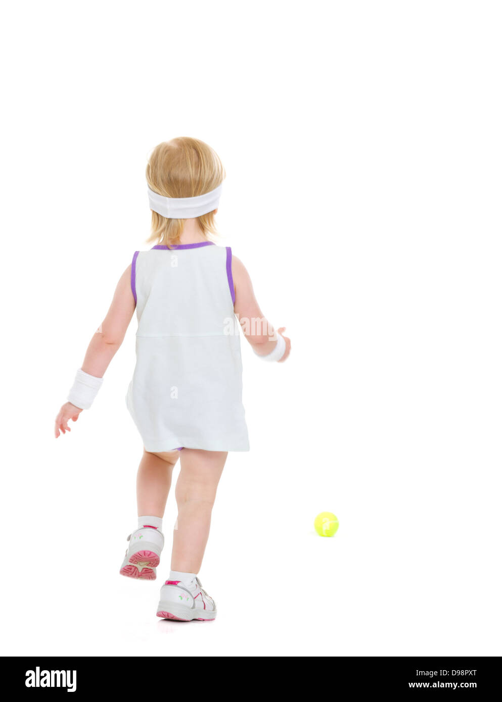 Baby running for tennis ball . rear view - Stock Image
