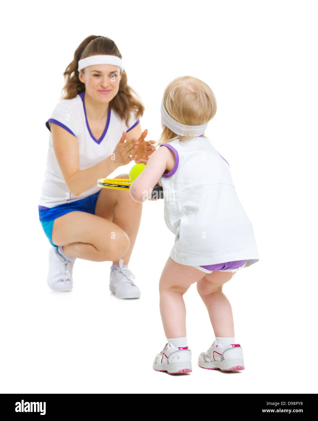 Mother and baby in tennis clothes playing tennis - Stock Image