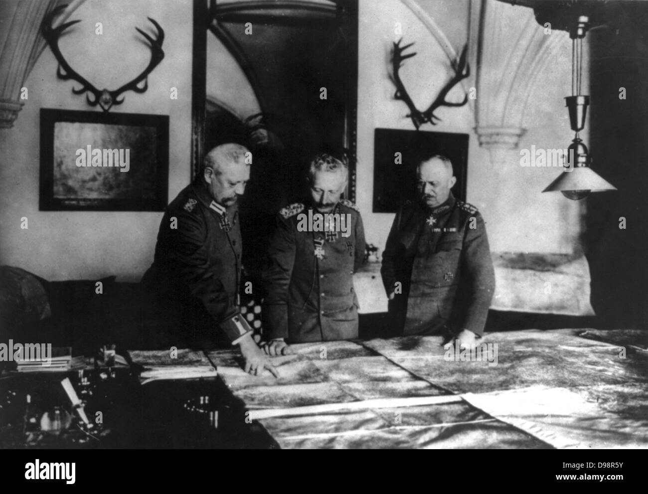 World War I: Wilhelm II of Germany studying maps with his senior commanders General Hindenburg, left, and General - Stock Image