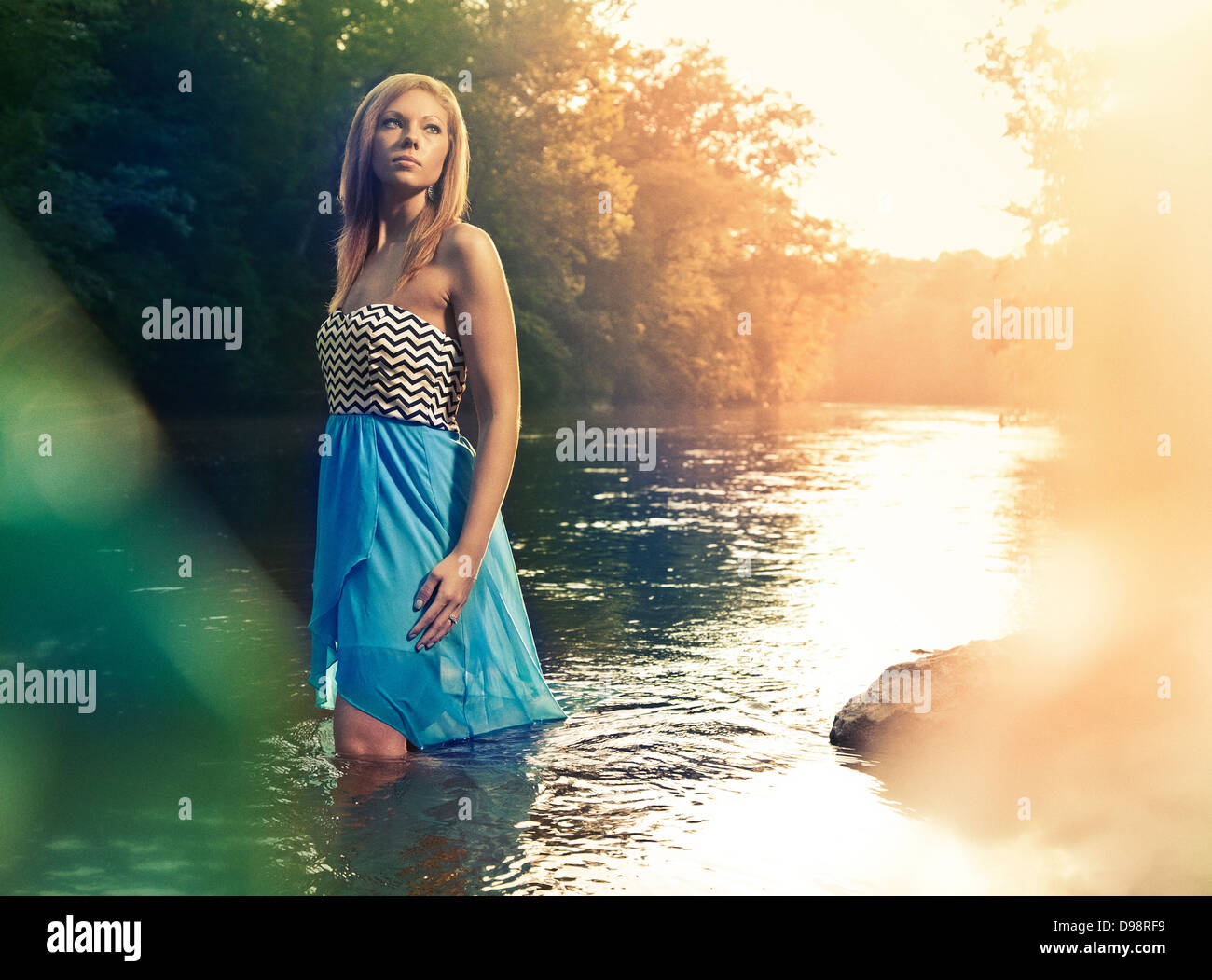 Woman in blue dress walking in river during sunset - Stock Image