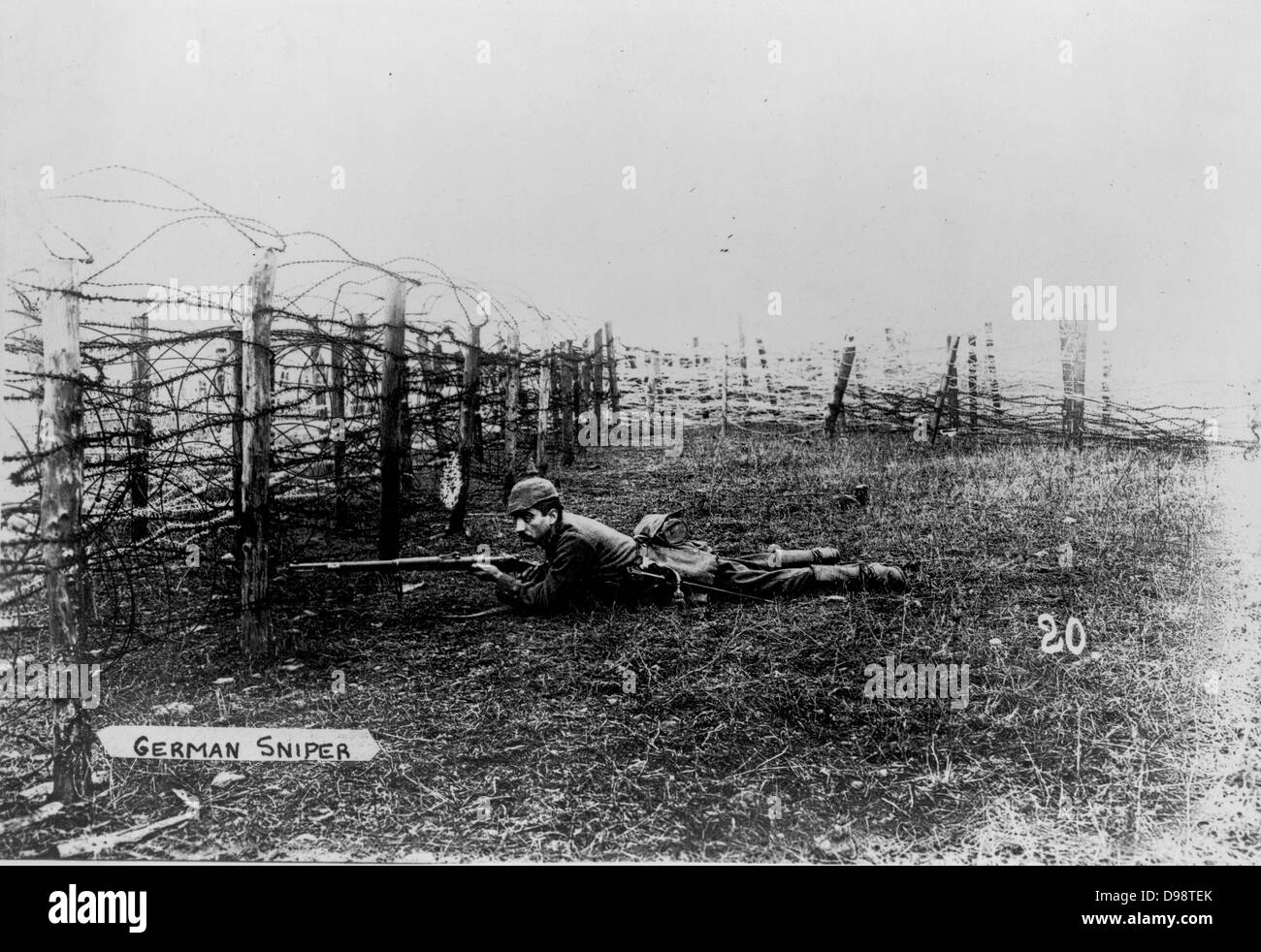 World War I 1914-1918: German sniper wearing a pickelhelm, lying on the ground behind barbed wire entanglements, - Stock Image