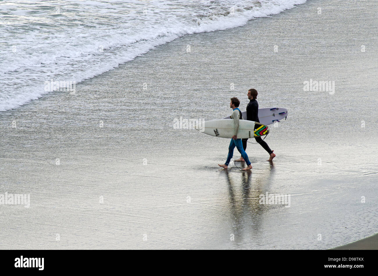 Two young wave surfers in Piha beach near Auckland, New Zealand Stock Photo