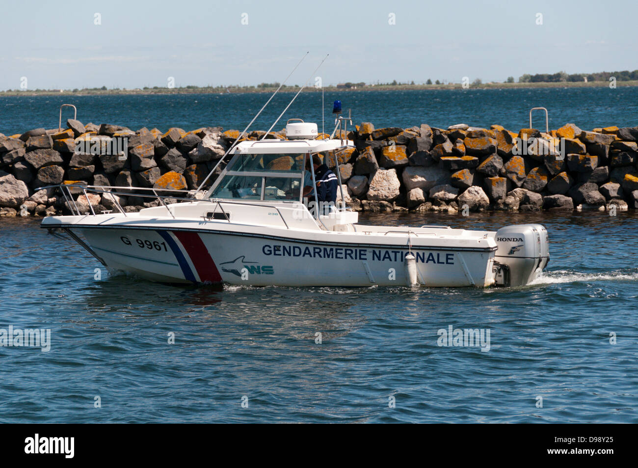 A boat of the French Gendarmerie Nationale leaving Marseillan harbour. - Stock Image