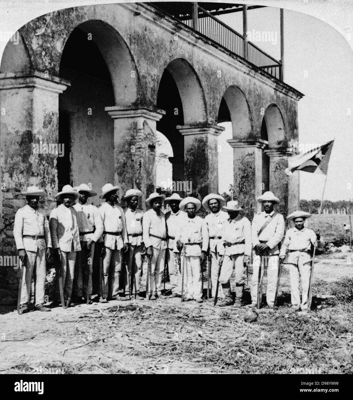 Officers of Gen. Gomez' Army, Remedios, Cuba.  Twelve men standing in front of a building, they are holding - Stock Image
