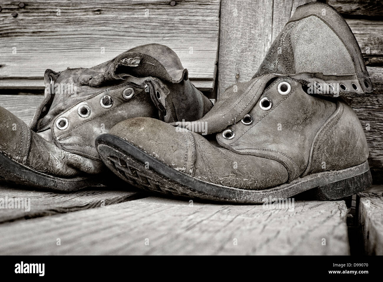 Black & white photo of old weathered hiking boots on wooden porch of Chitina Emporium, remote town of Chitina, Alaska, Stock Photo