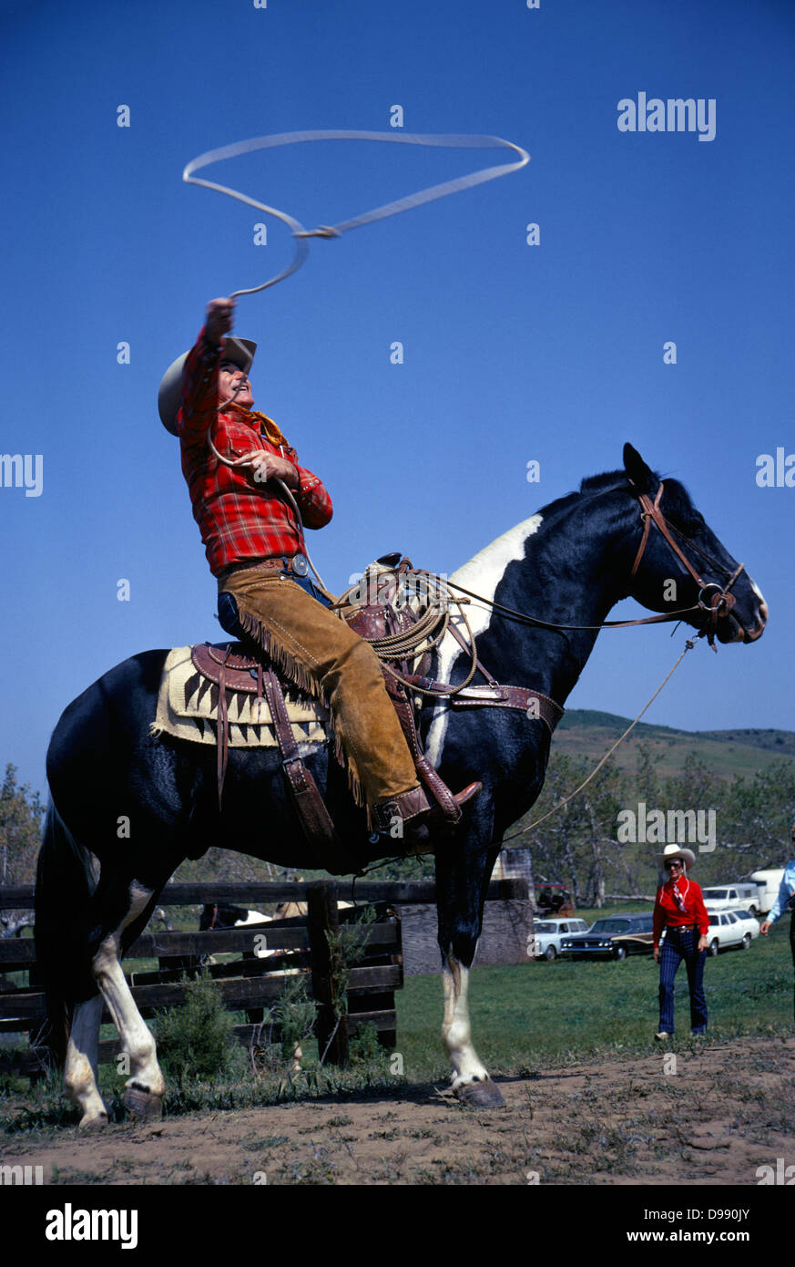 Famous cowboy, actor, and stuntman Montie Montana practices on horseback with his roping lariat prior to a rodeo - Stock Image