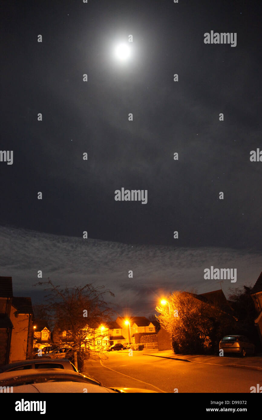 Winter's moon hanging over town houses in Faringdon, Oxfordshire, lit by streetlights - Stock Image