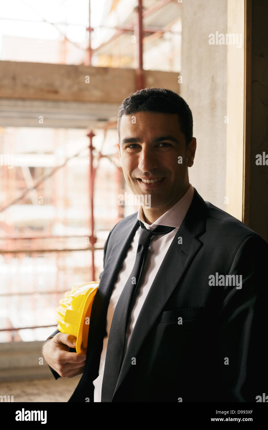 portrait of male engineer smiling and looking at camera in construction site - Stock Image