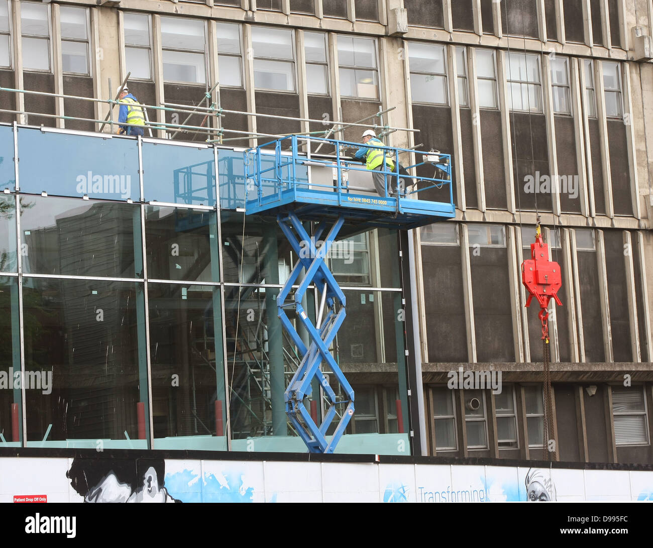 Builders working at heights in a Mobile Elevating Working Platform aka MEWP outside the Bristol Royal Infirmary - Stock Image