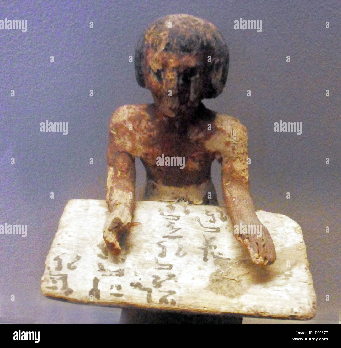 Egyptian tomb figure depicting a scribe. - Stock Image