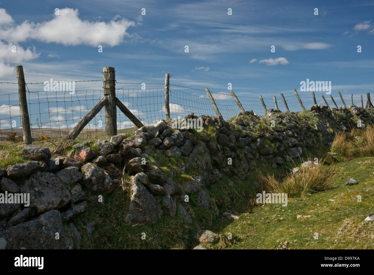 Long dry stone wall and wire fence stretched across farmland Stock ...
