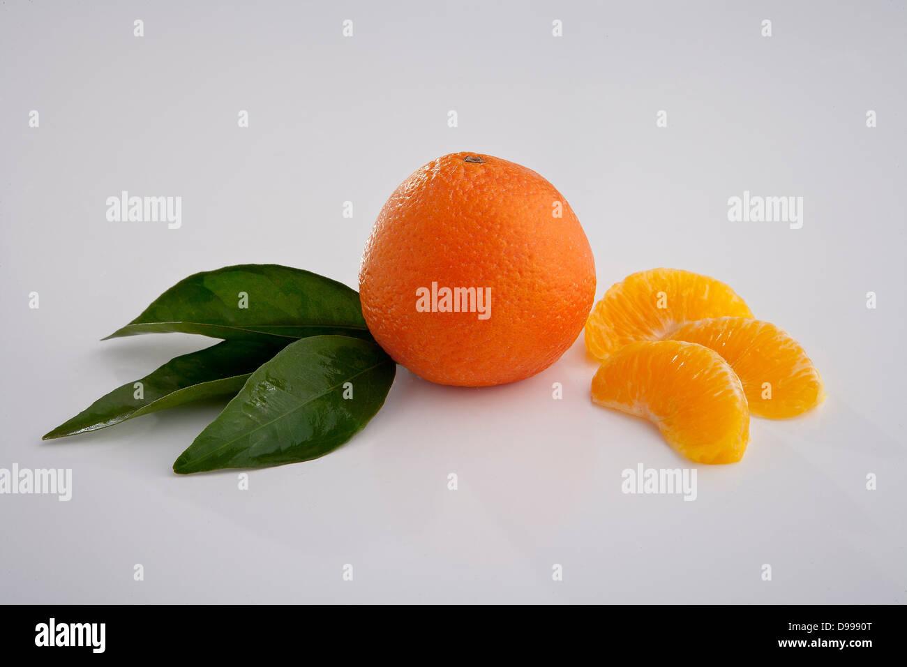 oranges and orange wedges on white - Stock Image
