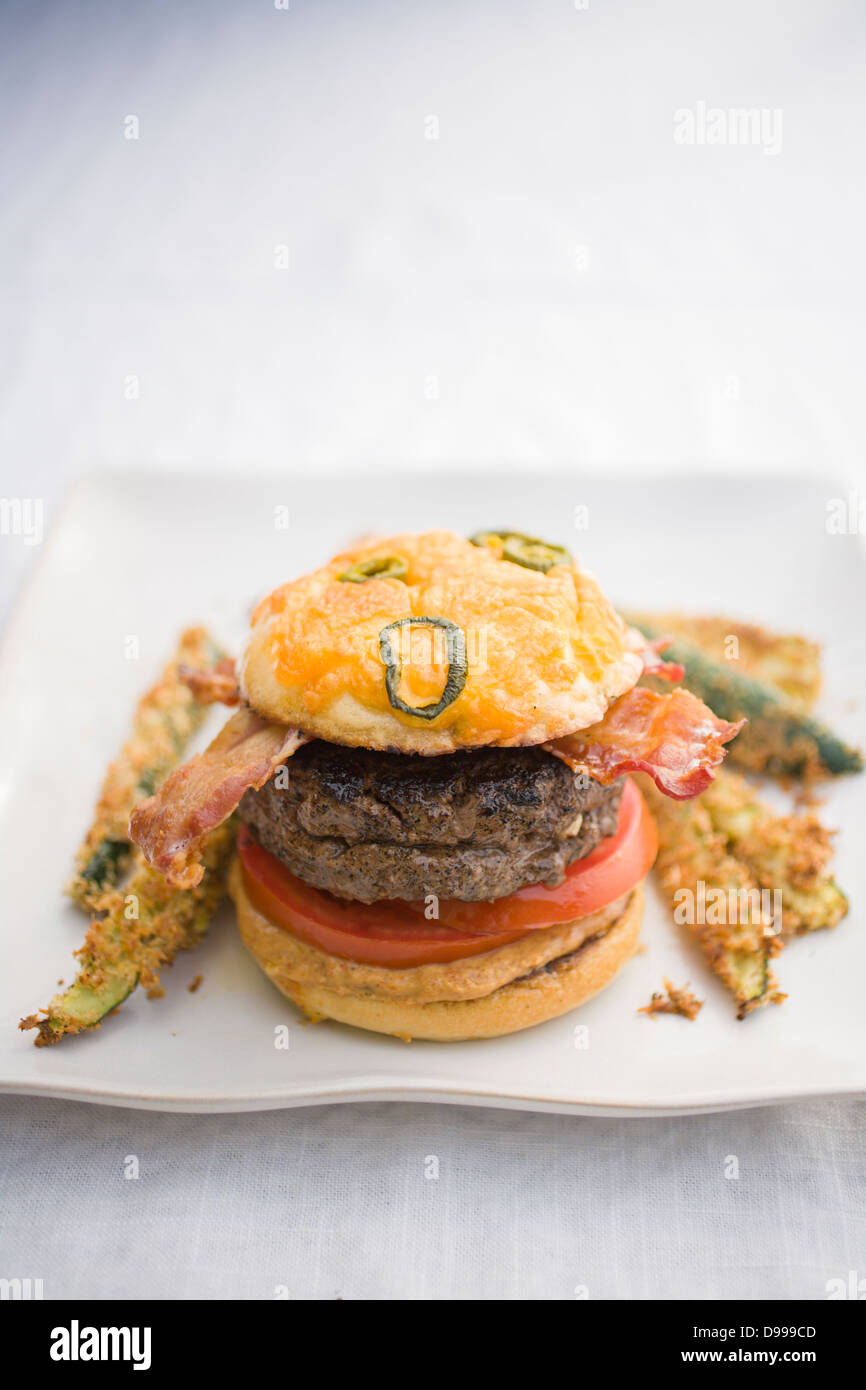 burger bacon tomatoes mustard jalapeno cheese bun and zucchini fries - Stock Image