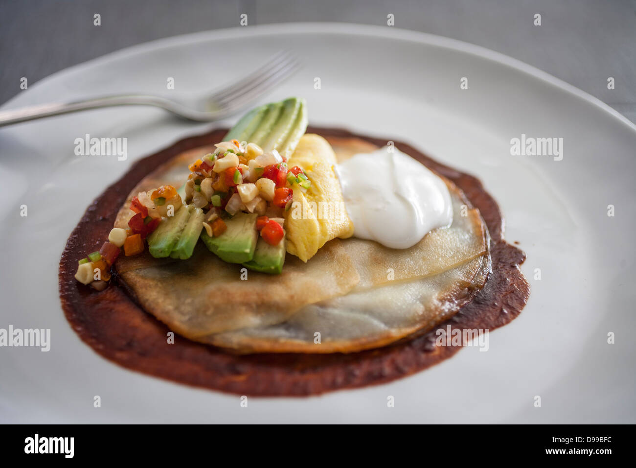 huevos rancheros with fresh cut avocado and sourcream - Stock Image