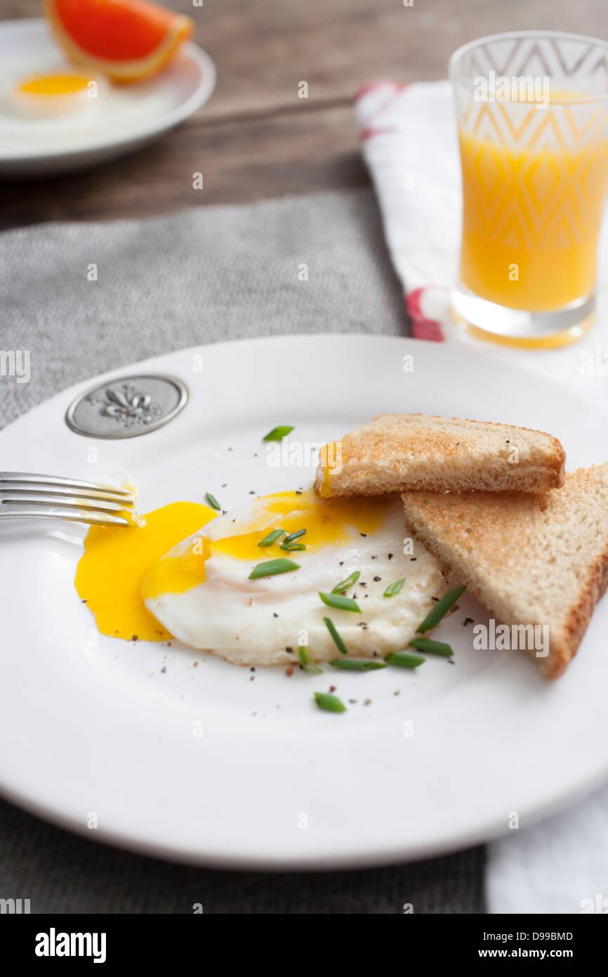fried egg and toast with orange juice - Stock Image