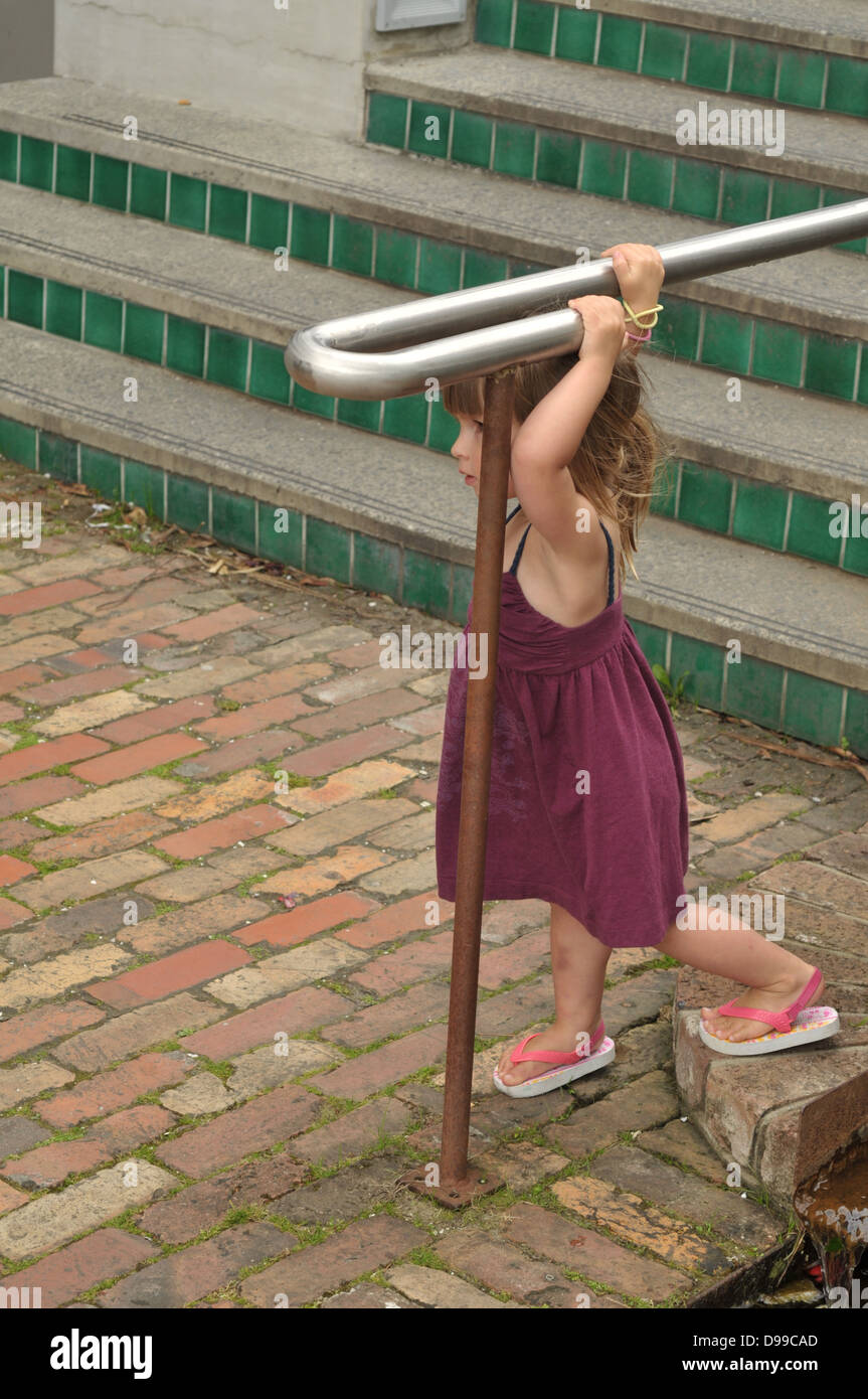 a37d07e198afa Young girl wearing summer dress and jandals leaning to stairs railing -  Stock Image
