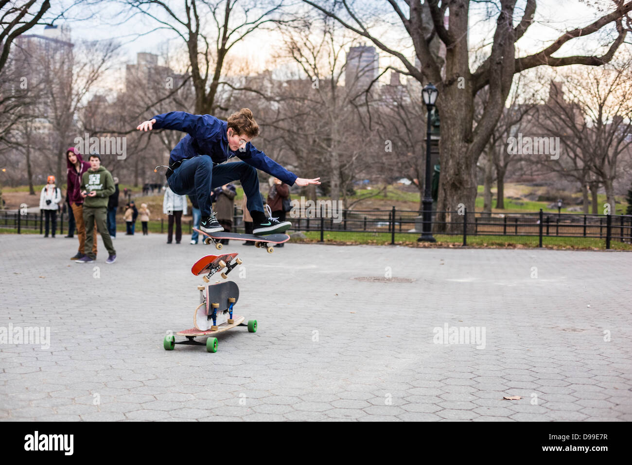 A young skateboarder executing an acrobatic jump in Central Park, New York City - Stock Image