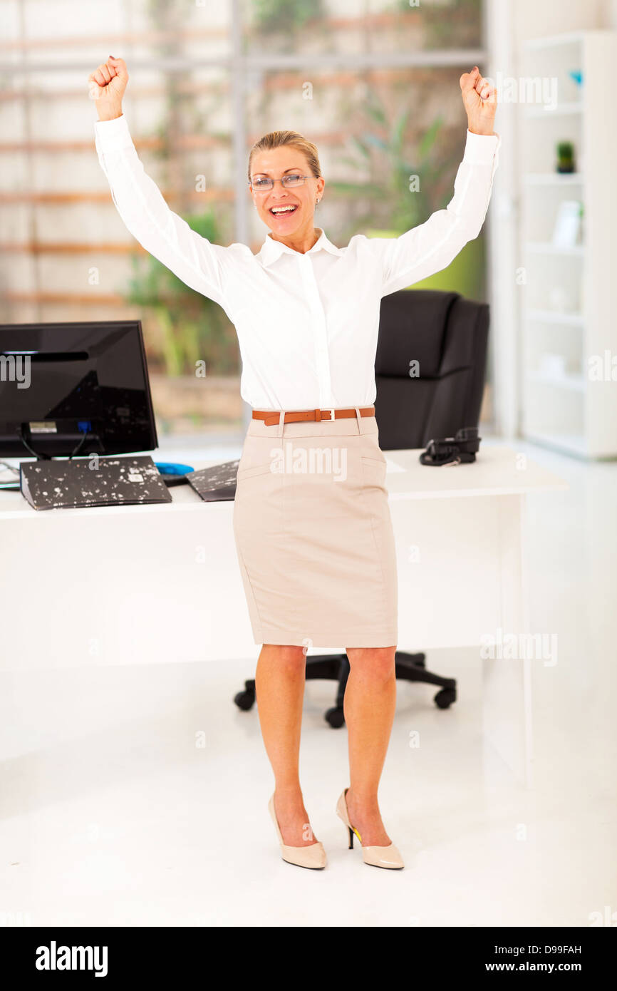 cheerful senior businesswoman waving fists in office - Stock Image