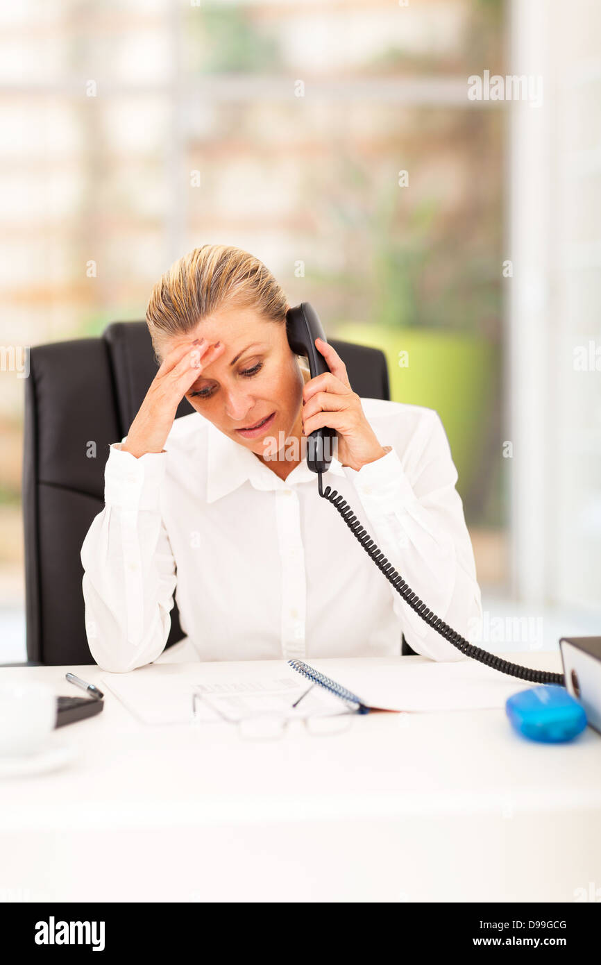 worried senior businesswoman talking on the phone in office - Stock Image