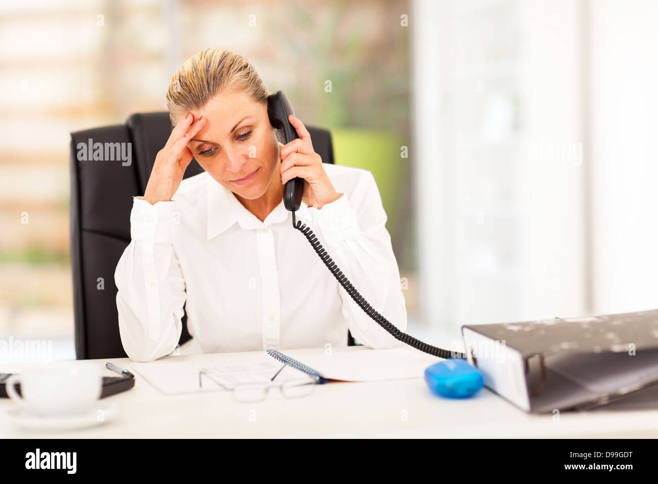 serious middle aged businesswoman talking on phone - Stock Image