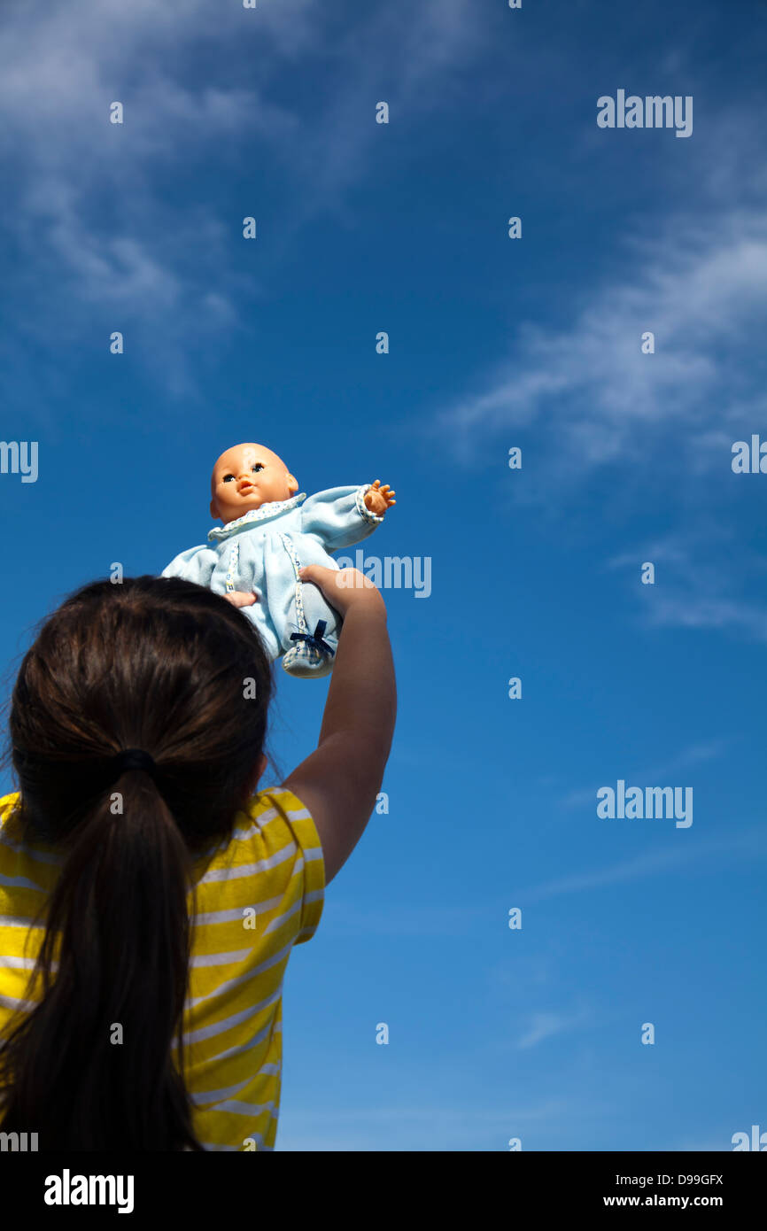 Girl holding baby doll to sky