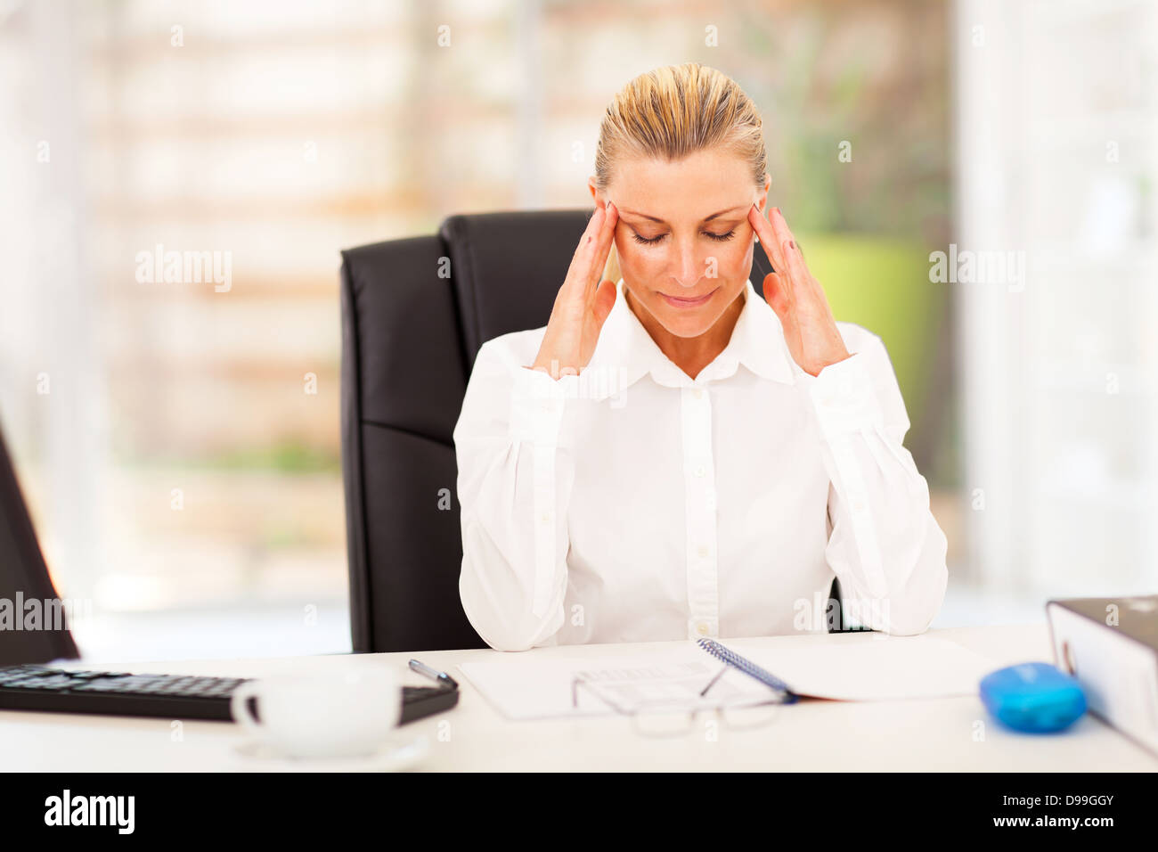 elegant female middle aged office worker resting in office - Stock Image