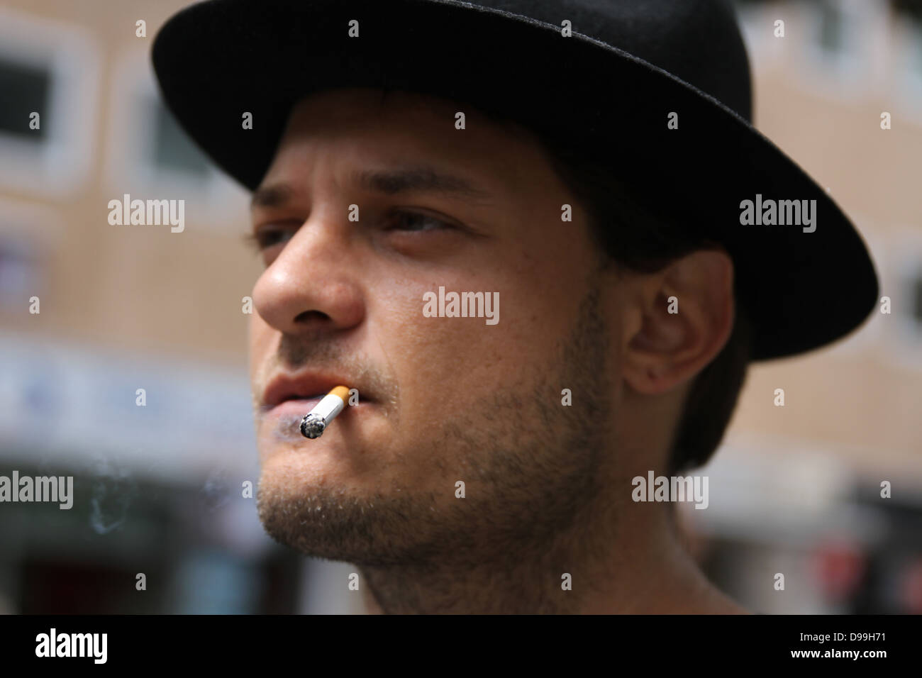 Man in hat smoking a cigarette - Stock Image