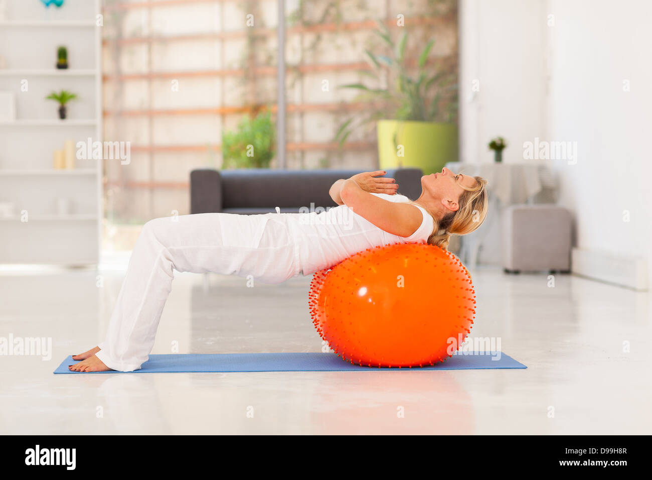 mature woman working out with exercise ball at home - Stock Image