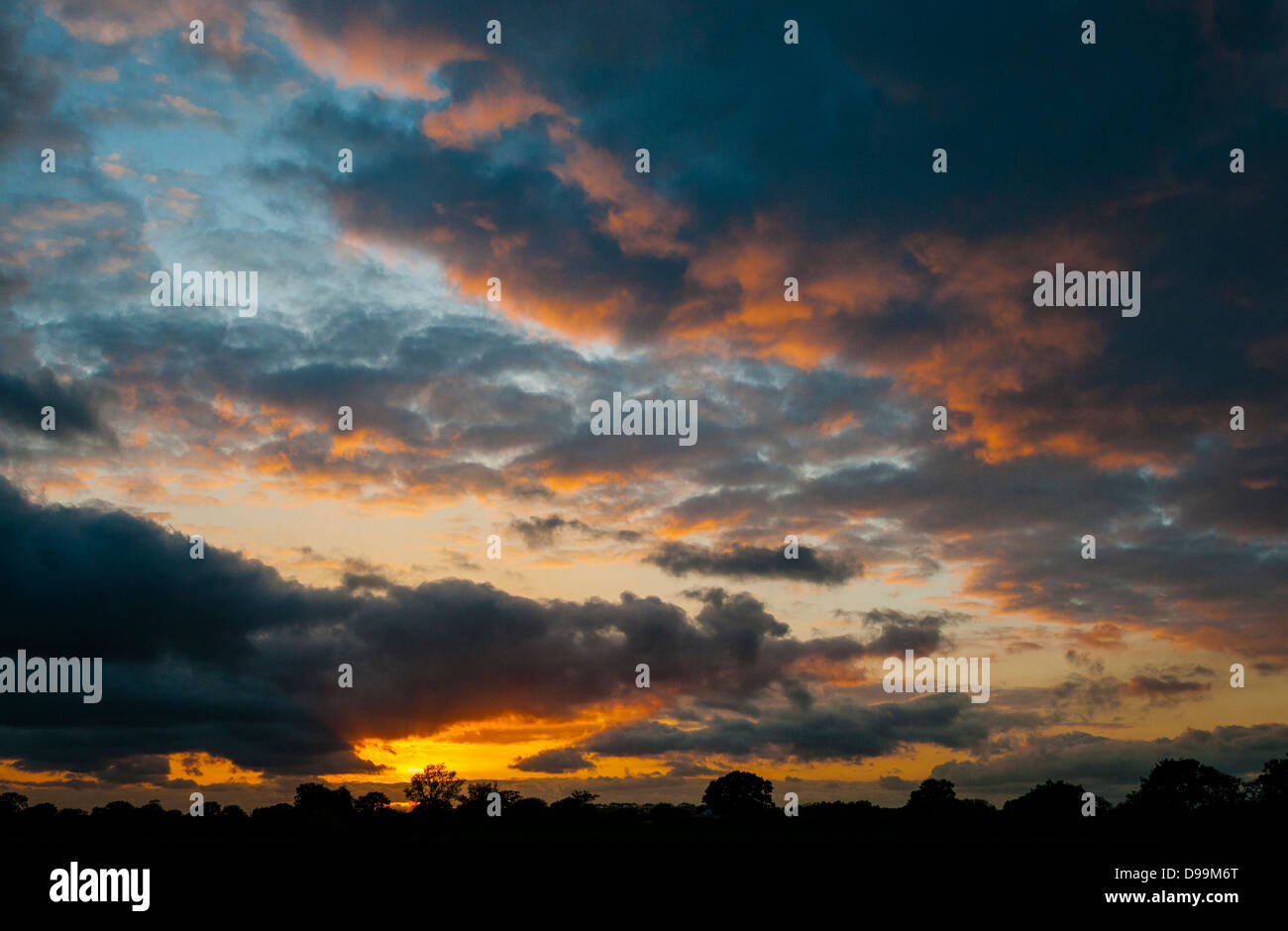 Clouds illuminated by sunset, over countryside horizon. - Stock Image