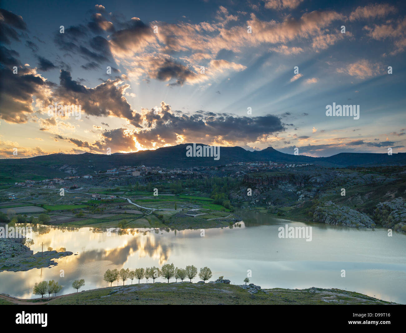 Clouds illuminated by rising sun and reflected in the lake - Stock Image