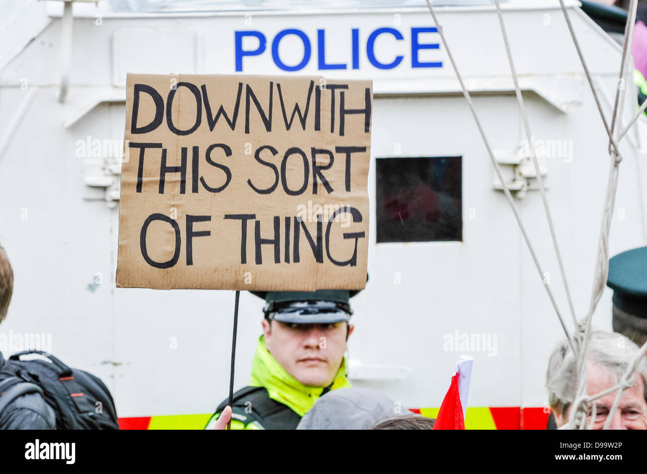 Belfast, Northern Ireland. 15th June 2013. A handwritten banner is held up in front of a policeman saying 'Down - Stock Image